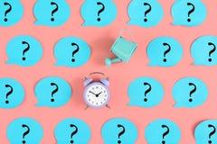 На розовой предпосылке, наклеены много голубых стикеров с вопросительными знаками Среди их, будильника и голубого мочить Стоковое Изображение RF