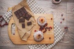 На светлой деревянной столешнице на салфетке белья checkered, деревянная разделочная доска с булочками взбрызнутыми с напудренным стоковое фото
