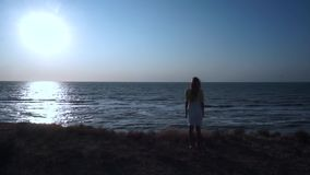 На скале, край земли, на желтой траве, стоит недвижная девушка в желт-белом платье, с длиной белокурым видеоматериал