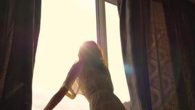 На солнечном утре счастливая женщина раскрывает занавесы окном в спальне акции видеоматериалы