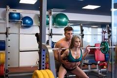 На спортзале Девушка помощи инструктора для того чтобы сделать сидение на корточках Стоковое фото RF