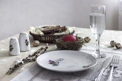 На стекле ножа вилки красного цвета яичка плиты гнезда пасхи соли перца хлеба воды Стоковые Изображения RF