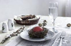 На стекле ножа вилки красного цвета яичка плиты гнезда пасхи соли перца хлеба воды Стоковые Изображения