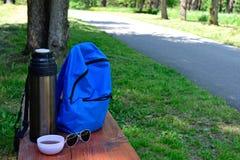 На стенде thermos, рюкзак, стекла и чашка чаю стоковое изображение