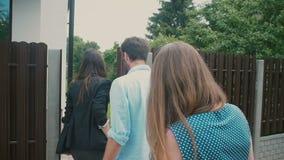 На стробах молодая пара говорит к деловому брюнет которое водит их к Белому Дому Медленный mo, съемка Steadicam сток-видео