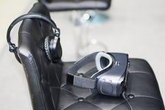 На стуле стекла для виртуальной реальности с наушниками стоковая фотография