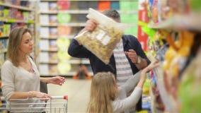 На супермаркете: Счастливая семья из трех человек, держа руки, прогулки через раздел свежей продукции магазина отец видеоматериал