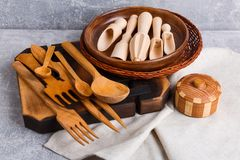 На таблице доска и корзина в которой комплект различных приборов кухни сделанных из древесины Стоковая Фотография