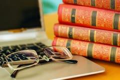 На таблице книги в красной крышке и компьтер-книжке Стоковое Изображение