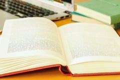 На таблице книги в красной крышке и компьтер-книжке Стоковая Фотография RF