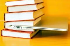 На таблице книги в красной крышке и компьтер-книжке Стоковые Изображения RF