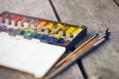 На таблице краска акварели, вместе с которой мать-и-мачеха цветков и щетки стоковая фотография