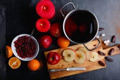 На таблице лоток с sangria, яблоки и апельсин, плита с клюквами и горящие свечи Стоковое Изображение
