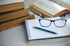 На таблице положите энциклопедии, тетрадь, карандаш, стекла и книгу с диаграммами стоковые фотографии rf