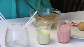 На таблице стекла с замороженностью для попов торта и палочками для их Женщина свертывает шарики печенья Варить застекленный для  акции видеоматериалы
