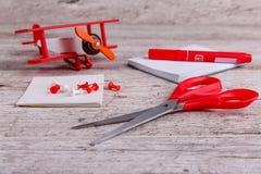 На таблице тетради, самолет игрушки, отметка, струбцины и ножницы Конец-вверх стоковое фото rf