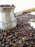 На таблице cezve, заполненное с кофейными зернами Разбрасывают другие кофейные зерна вокруг стоковое изображение rf