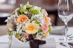 На таблице стоит bridal стекла букета и шампанского Стоковые Изображения