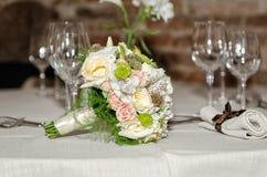 На таблице стоит bridal стекла букета и шампанского Стоковые Фотографии RF