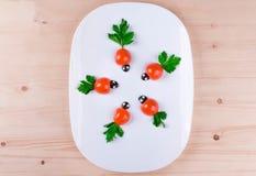 На томатах, петрушке и oliv белых плиты красиво положенных вне Стоковые Фотографии RF