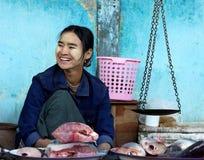 Надувательство fishmonger некоторые рыбы с традиционными масштабами в влажном рынке 4-ого января 2011 в bagan рынке, Мьянме Стоковое Изображение