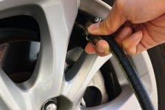 Надувать колеса автомобиля через насос Стоковая Фотография