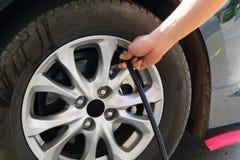 Надувать колеса автомобиля через насос Стоковые Изображения