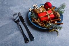 На украшениях плиты ели, снежинок, циннамона и грецких орехов, шариков и подарочной коробки, рядом с, столовый прибор Стоковое Фото