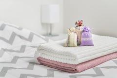 Надушенные саше на полотенцах на кровати Душистые мешки для уютного дома Высушенная лаванда в сумках украшения в спальне Стоковые Фото
