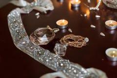 Надушите и браслет, горящие свечи, лента при серебряные камни лежа на деревянном столе Стоковая Фотография RF