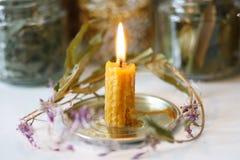 На фоне опарников с высушенными травами, ожога свечи воска с красивым пламенем стоковые фотографии rf
