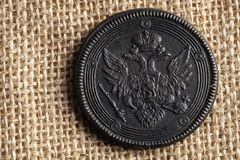 На холсте ткань старая русская монетка с двуглавым орлом, медная монетка Стоковая Фотография