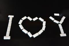 На черной лоснистой предпосылке, белые подушки от жевательной резины с отражением положены и лежат в форме влюбленности я тебя лю Стоковые Изображения RF