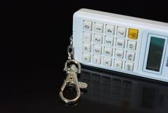 На черной лоснистой предпосылке кнопки от белого калькулятора с штуцером металла и отражением Стоковое Изображение RF