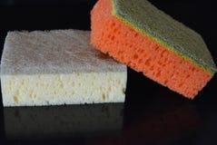 На черной лоснистой предпосылке, положены 2 губки кухни, и губки dishwashing желтого и оранжевого цвета с отражением Стоковые Фотографии RF