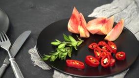 На черной плите отрезанный томат и персик, рядом с ним sprig розмаринового масла, рядом с плитой вилка с ножом видеоматериал