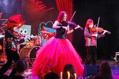 На этапе, выразительные рыжеволосые сыновьья Марии Bessonova скрипача дублируют поколения трио 2 скрипки красных пламенистых музы Стоковое Фото