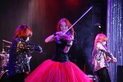 На этапе, выразительные рыжеволосые сыновьья Марии Bessonova скрипача дублируют поколения трио 2 скрипки красных пламенистых музы Стоковые Изображения