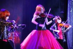 На этапе, выразительные рыжеволосые сыновьья Марии Bessonova скрипача дублируют поколения трио 2 скрипки красных пламенистых музы Стоковые Фотографии RF