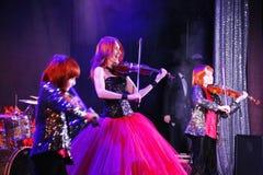 На этапе, выразительные рыжеволосые сыновьья Марии Bessonova скрипача дублируют поколения трио 2 скрипки красных пламенистых музы Стоковая Фотография