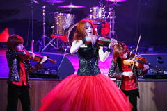 На этапе, выразительные рыжеволосые сыновьья Марии Bessonova скрипача дублируют поколения трио 2 скрипки красных пламенистых музы Стоковое фото RF