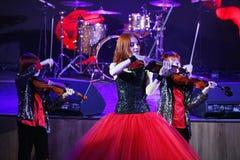 На этапе, выразительные рыжеволосые сыновьья Марии Bessonova скрипача дублируют поколения трио 2 скрипки красных пламенистых музы Стоковые Изображения RF