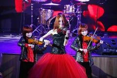 На этапе, выразительные рыжеволосые сыновьья Марии Bessonova скрипача дублируют поколения трио 2 скрипки красных пламенистых музы Стоковая Фотография RF