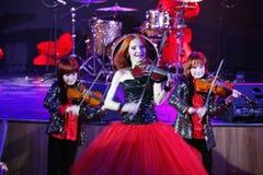 На этапе, выразительные рыжеволосые сыновьья Марии Bessonova скрипача дублируют поколения трио 2 скрипки красных пламенистых музы Стоковое Изображение RF