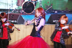 На этапе, выразительные рыжеволосые сыновьья Марии Bessonova скрипача дублируют поколения трио 2 скрипки красных пламенистых музы Стоковое Изображение