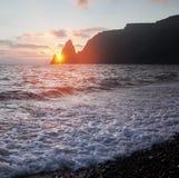 На seashore заходящее солнце прячет за мощными прибрежными скалами Стоковые Изображения