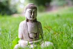 Небольшая белая статуя Будды в представлении раздумья на зеленую естественную яркую предпосылку Религиозный символ буддизма стоковые изображения rf