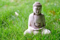 Небольшая белая статуя Будды в представлении раздумья на зеленую естественную яркую предпосылку Религиозный символ буддизма стоковое изображение