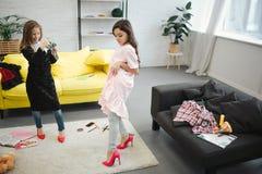 Небольшая белокурая девушка фотографируя ее друг на камере в комнате Брюнет представляя и смотря вниз Носка обоих подростков стоковое фото