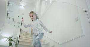 Небольшая девушка 6 лет в утре в лестницах современных дизайна дома она приходя вниз на первый этаж акции видеоматериалы